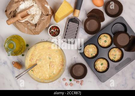Preparación Mffins caseros salados con queso parmesano, salchichas o jamón y guisantes verdes para el desayuno. Harina, huevos y otros ingredientes en el mármol