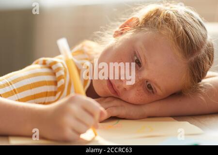 Retrato en tonos cálidos de cuadros de dibujo de niña de cabello rojo mientras se acostaba la cabeza sobre la mesa bajo la luz del sol