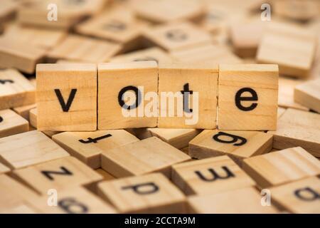 """Cartas de madera que componen la palabra """"votar"""" sobre un fondo de cartas dispersas derramadas sobre una tabla de madera"""