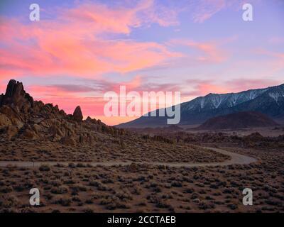 Puesta de sol detrás de formaciones rocosas en un árido paisaje desértico.