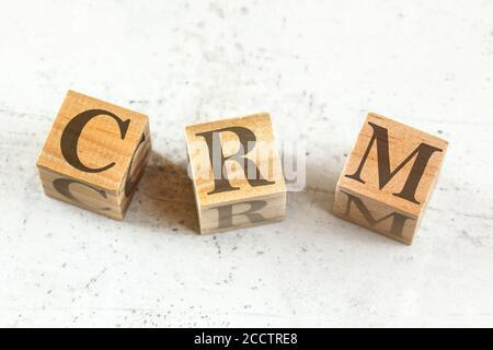 Tres cubos de madera con letras CRM - significa Gestión de la relación con el cliente - en pizarra blanca.
