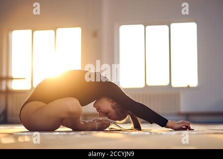 Elegante gimnasia de arte flexible vestida con una barda negra sentada en un suelo de color claro, estirando el cuerpo intensamente hacia delante, tiro lateral, gimnasia rítmica