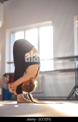 Mujer cansada y flexible con pelo largo y en negro sportswear, se encuentra en posición de lucio, cruzando las manos alrededor de las piernas, preparándose para los entrenamientos