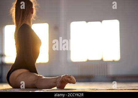 Elegante mujer bonita se sienta en el suelo de color claro haciendo divisiones, volviendo la cabeza hacia atrás, mirando a la ventana, estirándose, preparándose para el ejercicio, blu