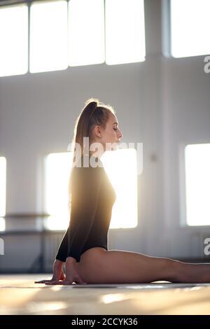 gymnast de arte elegante y talentoso sentado en el suelo con la espalda recta, mirando a un lado con la cara tranquila, vestido de negro sportswear, sobre el fondo de la hig