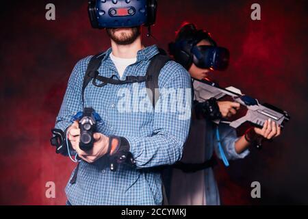 pareja aventureros se enfrentan de nuevo a la espalda sosteniendo armas virtuales, en lucha. Fondo ahumado aislado, luz roja de neón