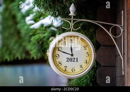 reloj clásico en la pared de un edificio de madera, el reloj muestra que sólo quedan unos minutos hasta 2021, año nuevo concepto