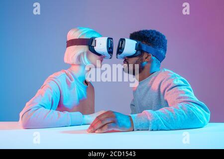Dos personas divertidas sentadas una frente a la otra y usando gafas de realidad virtual, pareja juguetona en gafas VR mirando una a la otra, de cerca lado vi