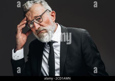 Hombre de negocios mayor en sus años 70 con pelo gris y barba con dolor de cabeza y frotar templos, mirando la cámara con ojos cansados y dolorosos, aislado