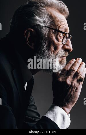 Pensive barbudo gris cabello elegante anciano hombre de negocios en traje negro formal, siendo profundo en los pensamientos, mantiene las palmas cerca de su barbilla, aislado sobre oscuro
