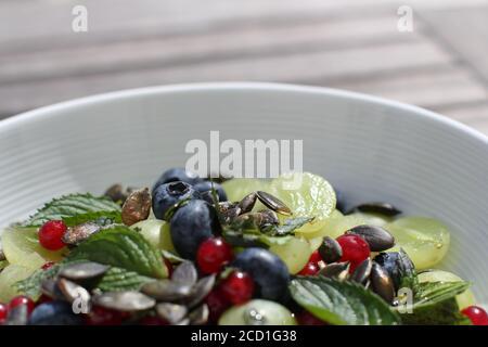 ensalada de frutas de colores con semillas de calabaza en la parte superior