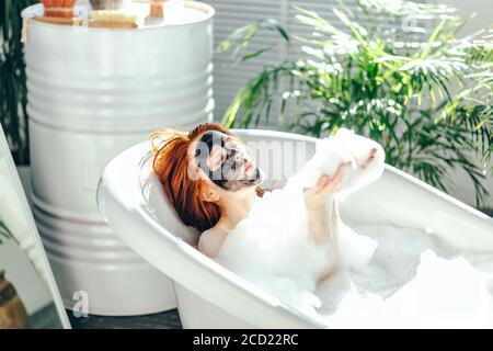 Encantadora mujer caucásica joven de pelo rojo disfrutando del spa en casa en el baño, tumbado en una bañera de espuma con máscara de barro negro en la cara, jugando w