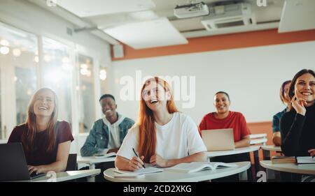 Grupo de estudiantes adolescentes sonriendo durante la conferencia en el aula. Estudiantes universitarios riendo en clase.