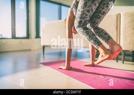 Yoga practicando a mano - niña principiante haciendo saltar a través de las manos en la esterilla de ejercicio en casa. Saltando con las piernas y los pies en el aire. Saldo de la base Foto de stock