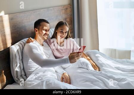 Vista superior de un impresionante marido guapo con cara sin afeitarse, estirando la mano con el teléfono celular por delante, tomando selfie junto con la joven esposa sentada en b.