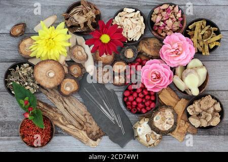 Hierbas chinas, especias y flores con agujas de acupuntura utilizadas en la medicina herbaria tradicional sobre fondo de madera rústica.