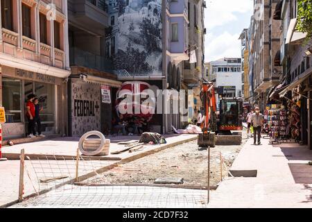 ESTAMBUL / TURQUÍA - 07.17.2020: Una excavadora trabajando en una construcción de carreteras en Karakoy durante el período pandémico de Covid 19. Gente sentada y hablando