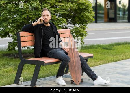 Hombre joven descansando, sentado con monopatín o longboard en un banco de madera, hablando en un teléfono inteligente.
