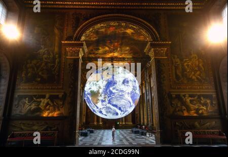 """Londres, Reino Unido. 28 de agosto de 2020. La espectacular obra de arte de Luke Jerram 'Gaia' está siendo exhibida en el Painted Hall como parte del Festival Internacional de Greenwich Docklands 2020 del 28 de agosto al 6 de septiembre. Gaia pretende inspirar el temor y el """"efecto de Visión general"""" para el planeta Tierra. La inmensa escultura de 7 metros es una réplica exacta del planeta con iluminación interna utilizando imágenes de la NASA, exhibidas a la música por Dan Jones. Crédito: Tommy London/Alamy Live News"""