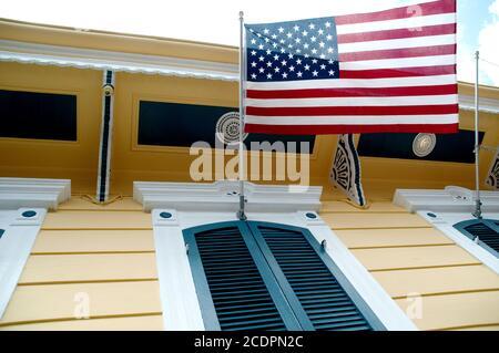 Una bandera americana, las estrellas y las rayas, colgando sobre la ventana con cierre de una escopeta amarilla, French Quarter, New Orleans, Louisiana, USA.