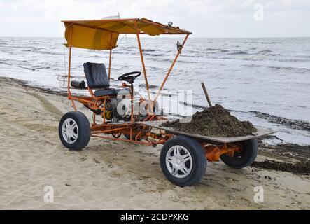 El coche para la recogida de basura de la playa. Limpieza en la playa, limpieza de la playa del barro y los residuos