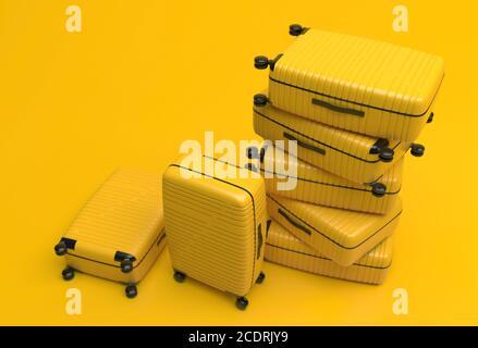 Muchas maletas amarillas idénticas en ruedas apiladas una encima de la otra. Las bolsas de viaje están en un montón sobre un fondo amarillo. Ilustración de renderización 3D. C