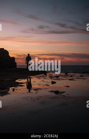 anónimo hombre viajero de pie cerca del monte y sin fin mar bajo espectacular cielo al atardecer que se refleja en el agua