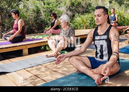 Joven y anciana en un grupo de personas Meditar en la postura del loto con los ojos cerrados durante la práctica del yoga en un complejo tropical en un día soleado