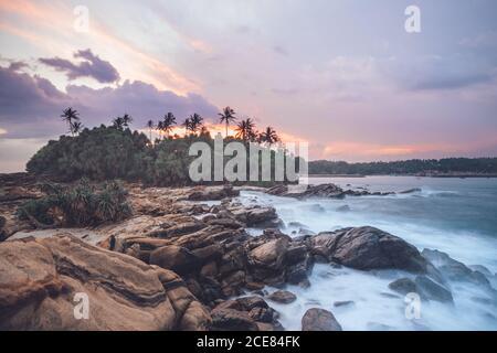 Increíble paisaje de costa rocosa y palmeras verdes cerca mar bajo el pintoresco cielo de la puesta de sol