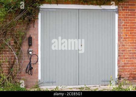 Una puerta de garaje gris con una toma eléctrica al lado para cargar coches eléctricos Foto de stock