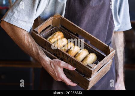 Desde arriba de la cosecha de panadero masculino irreconocible en el delantal de pie con caja de madera llena de sabrosos donuts recién horneados con superficie dorada y textura tierna