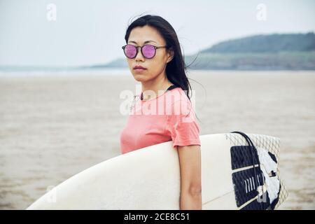 Joven surfista asiática femenina en traje de verano caminando sobre arena playa y llevar tablas de surf contra el mar azul calma Foto de stock