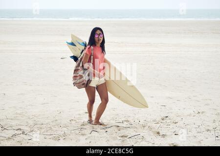 Surfista de toda la longitud joven asiática femenina en traje de verano caminando en la playa de arena y llevando tablas de surf contra el mar azul calma Foto de stock
