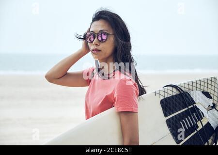 Joven surfista asiática femenina en traje de verano caminando sobre arena playa y llevando tabla de surf contra el mar azul calma mirando cámara Foto de stock