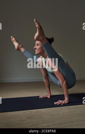 Vista lateral de la joven atleta fuerte feliz en leggings Balanceándose en los brazos mientras realiza Firefly asana durante la práctica de yoga