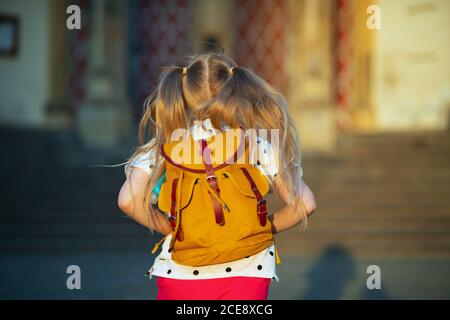 La vida durante la pandemia de covid-19. Visto desde detrás de la niña en blanco polka punto blusa con mochila amarilla yendo de la escuela fuera.