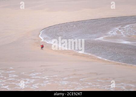 Los senderistas vistos desde una distancia caminando en la marea baja a través de Crantock Beach mientras el río Gannel fluye hacia el mar en Newquay en Cornwall.