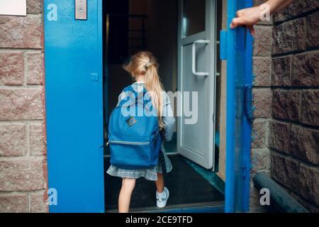 Vista trasera del padre vuelve a casa de la escuela con su hija cargando mochila