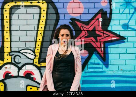 Joven mujer sonriente en ropa informal cerca de la pared de graffiti