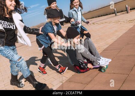 Grupo de niños de moda correr y divertirse mientras monta a una chica emocionada en monopatín bajo la luz del sol.