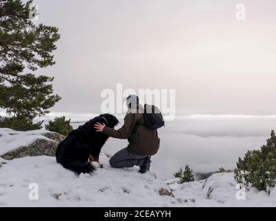 Hiker y su perro mirando en las montañas nevadas al fondo del cielo.