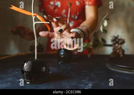 la mano tomando la inquietante manzana negra de halloween Foto de stock