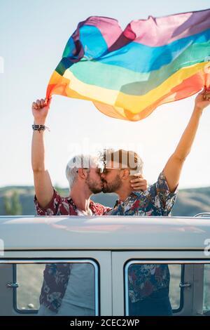 Dos hombres guapo besando y sosteniendo la bandera LGBT brillante mientras de pie dentro de la furgoneta con techo abierto en el campo en el sol día
