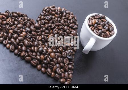 Granos de café con taza sobre fondo oscuro, en forma de corazón, primeros planos de vida, planos, estudio interior, me encanta el concepto de café
