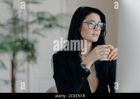 Foto de morena concentrada mujer copywriter bebidas café, trabajos en la tarea creativa, lleva gafas y traje negro formal, relojes webinar a.