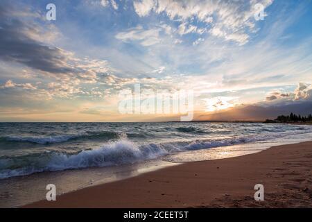 Hermosa puesta de sol en el lago. Las nubes brillantes se reflejan en el agua. Kirguistán.