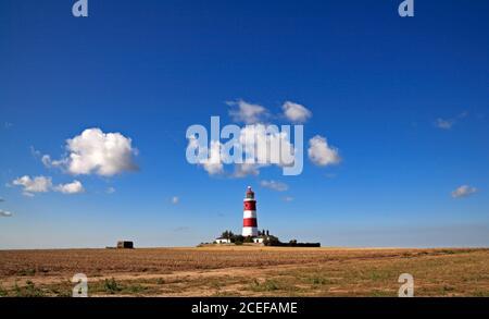 Una vista del faro de funcionamiento independiente contra un cielo azul con nubes blancas en la costa de North Norfolk en Happisburgh, Norfolk, Inglaterra, Reino Unido.