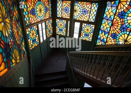 Elegante y colorido panel de vidrio manchado en la escalera de época en viejo y desvencijado edificio de madera con luz natural Foto de stock