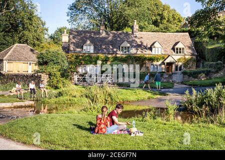 Los visitantes disfrutan de la luz del sol al lado del ford al otro lado del River Eye en el pueblo Cotswold de Upper Slaughter, Gloucestershire, Reino Unido