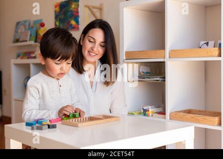 Lillte Kid jugando con un rompecabezas de madera de tetris y ayuda de madre o maestro. Resolución de problemas en casa. Comunidad de aprendizaje. Escuela Montessori